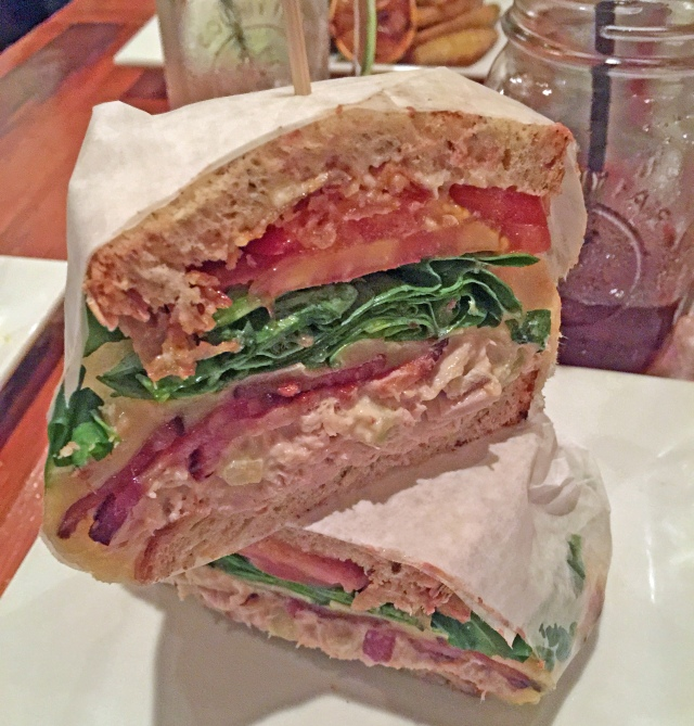 The Tuna Melt, fresh grilled tuna salad, melted havarti cheese, bacon, arugula, tomato, crispy shallots, mayo & dijon