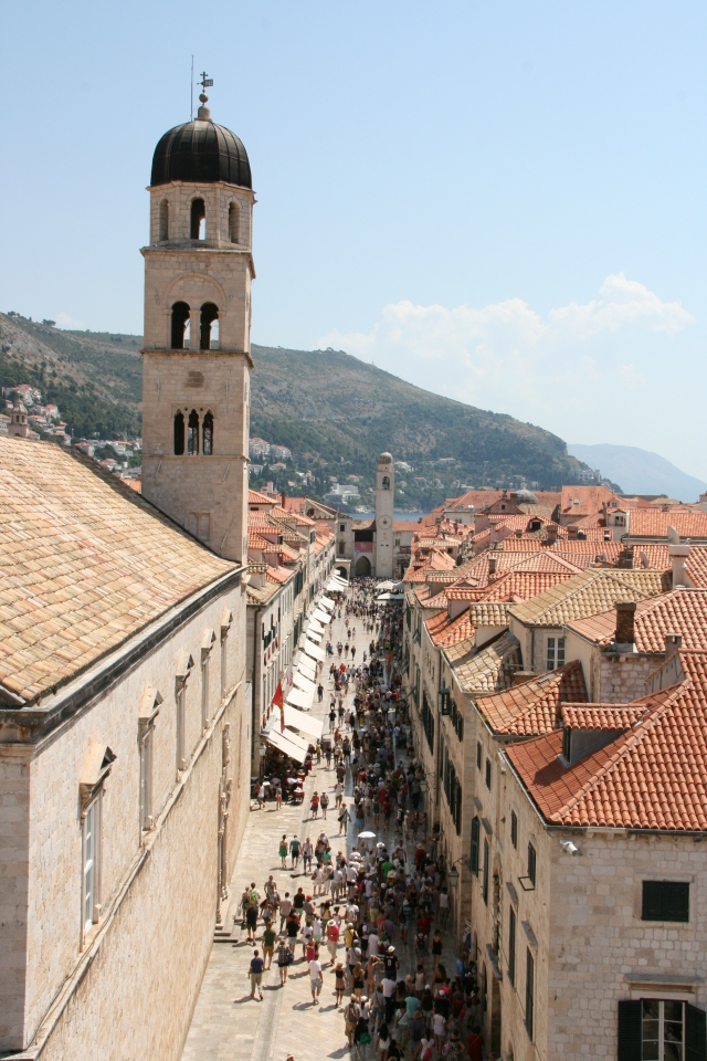 Crowds of tourists walking through the main street of the old city.